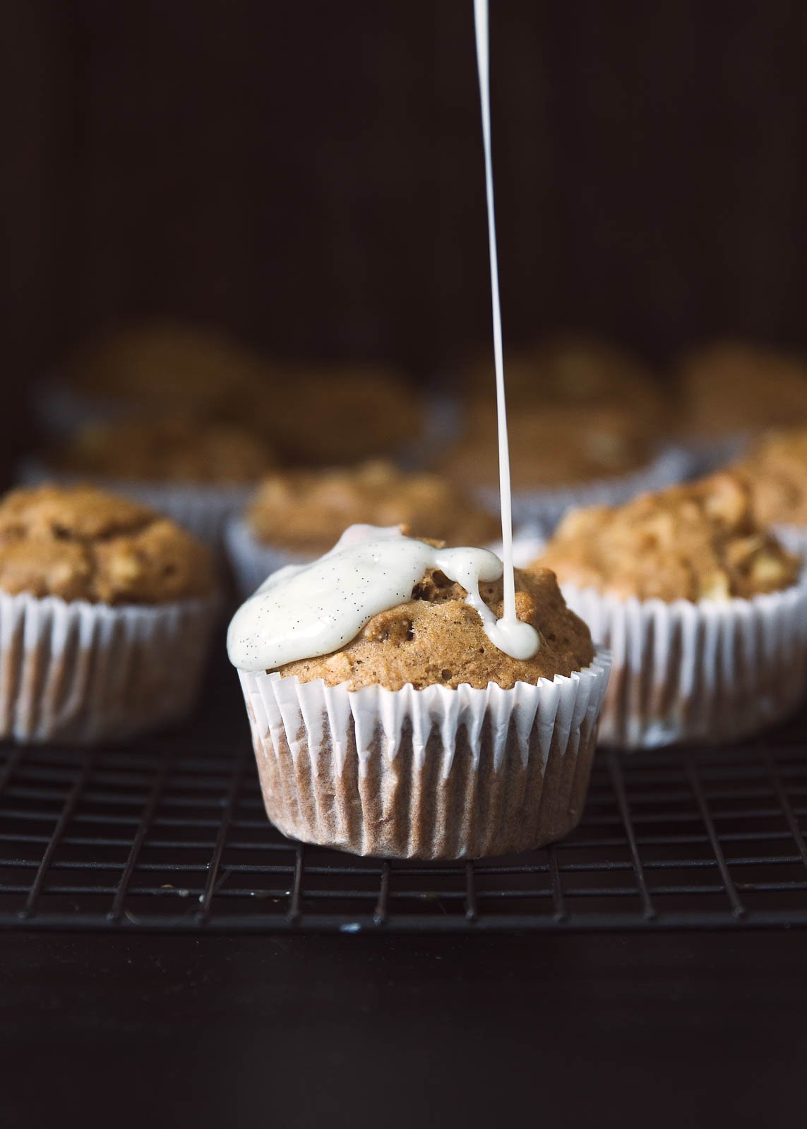 Healthy Apple Oatmeal Muffins being drizzled with vanilla glaze