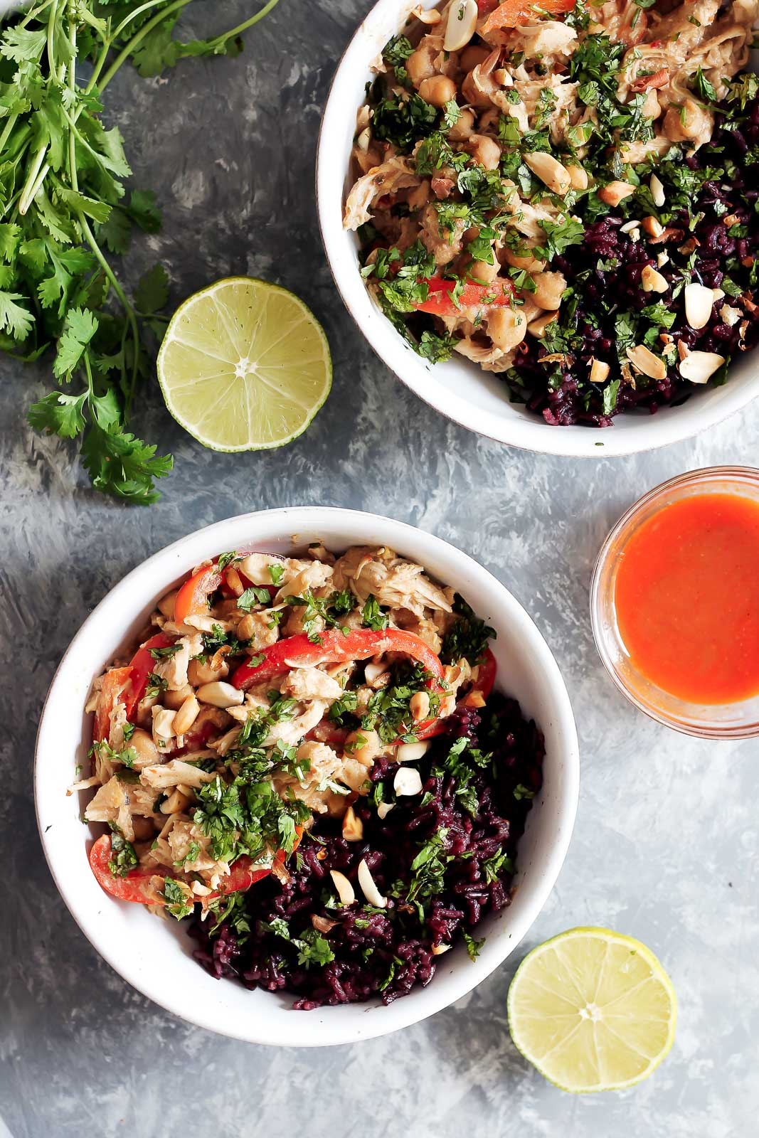 slow cooker thai peanut chicken with purple rice in two bowls