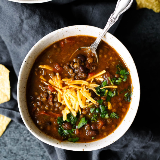 Slow Cooker Taco Lentil Soup in a bowl topped with cheese