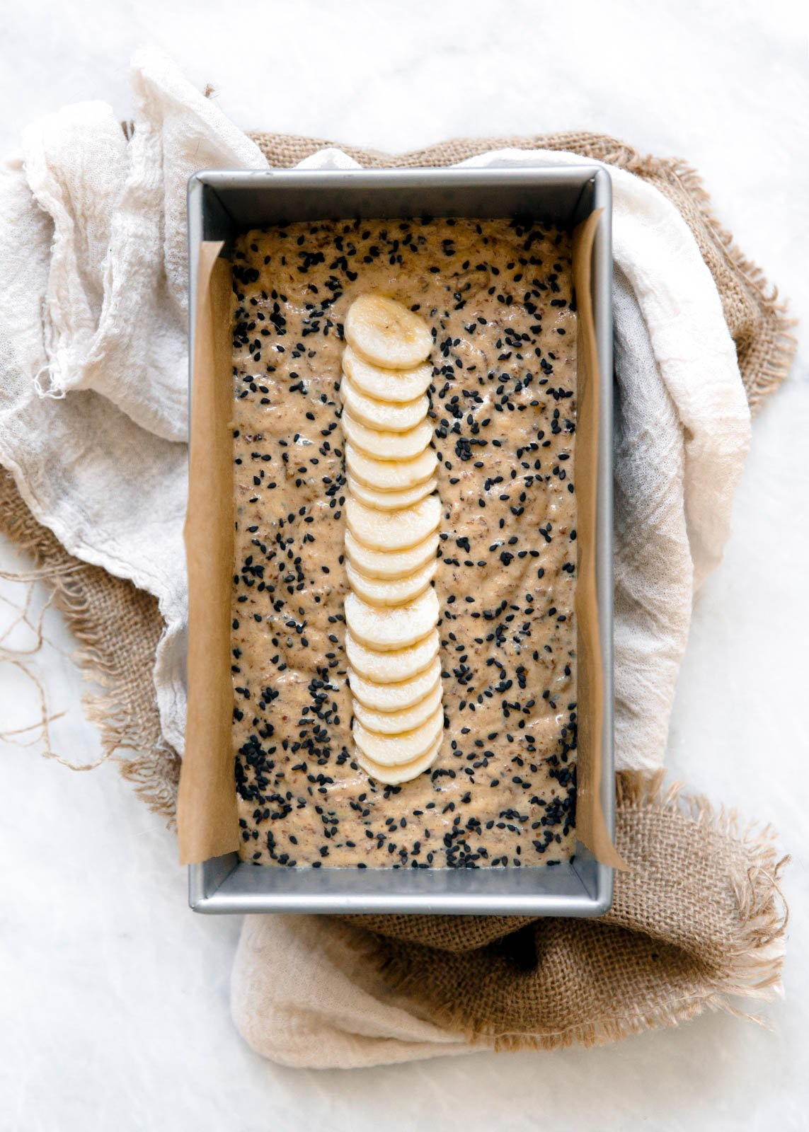 tahini banana bread batter in a loaf pan sitting on a counter with a towel underneath