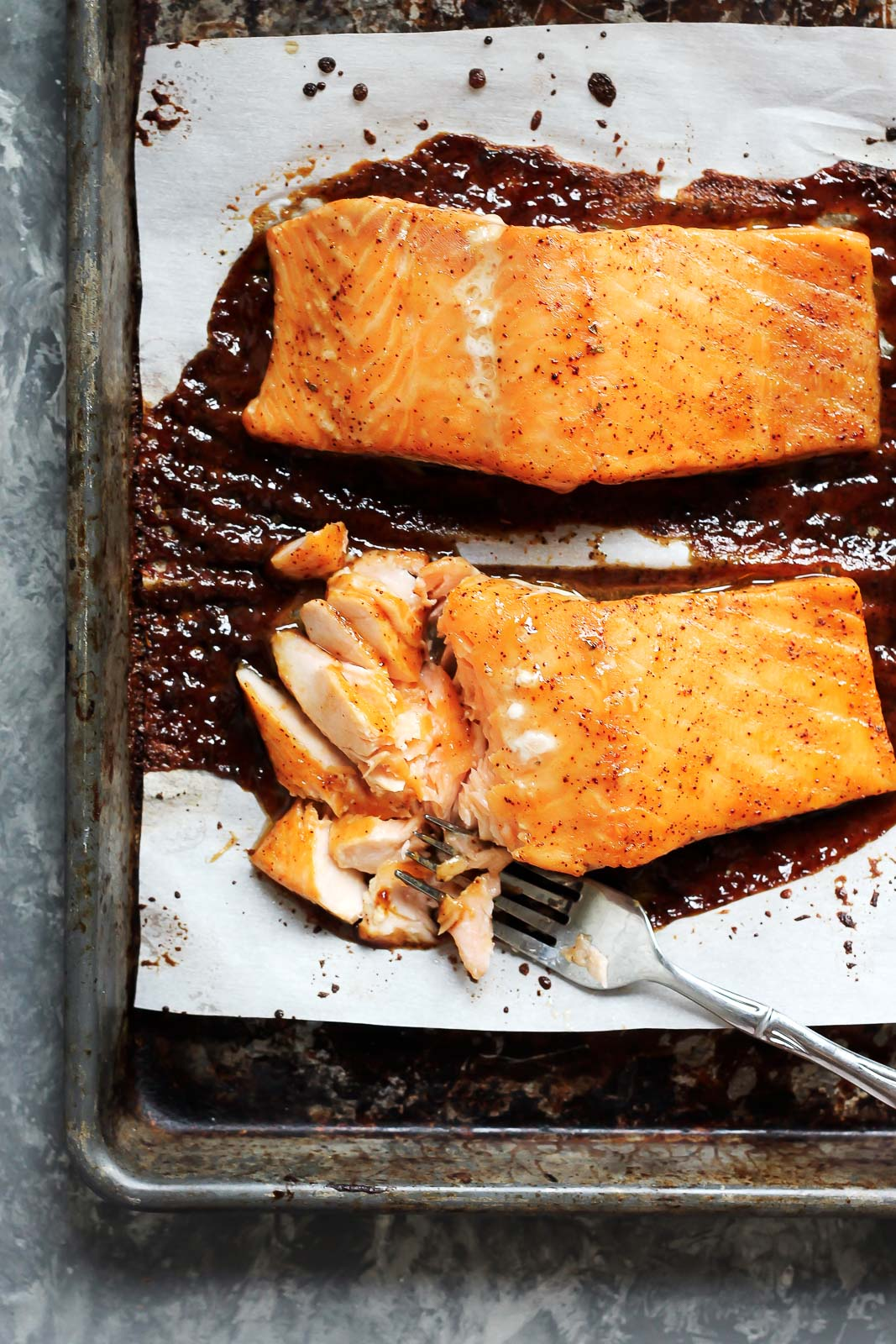 Two pieces of salmon on a baking sheet with a fork