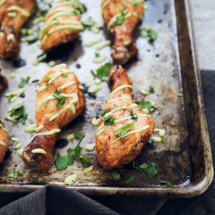 Peruvian Chicken Drumsticks are marinated with lime, garlic, peruvian spices and yogurt; then baked to perfection and drizzled with an avocado lime sauce! Serve with brown rice for a full meal!