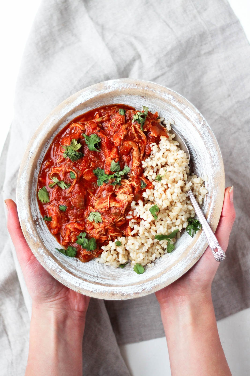 hands holding Slow Cooker Chicken Tikka Masala in a bowl with rice