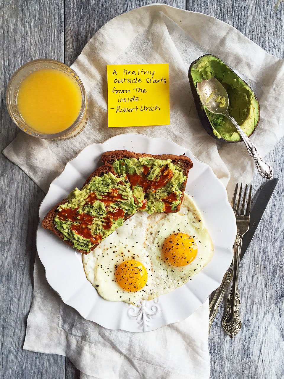 eggs and avocado toast on a plate next to a glass of orange juice