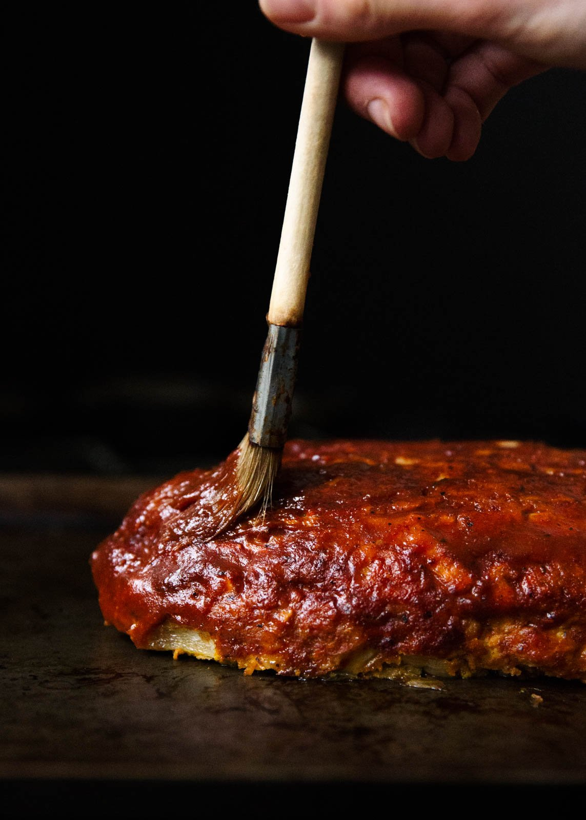 brushing healthy sweet potato BBQ turkey meatloaf with BBQ sauce