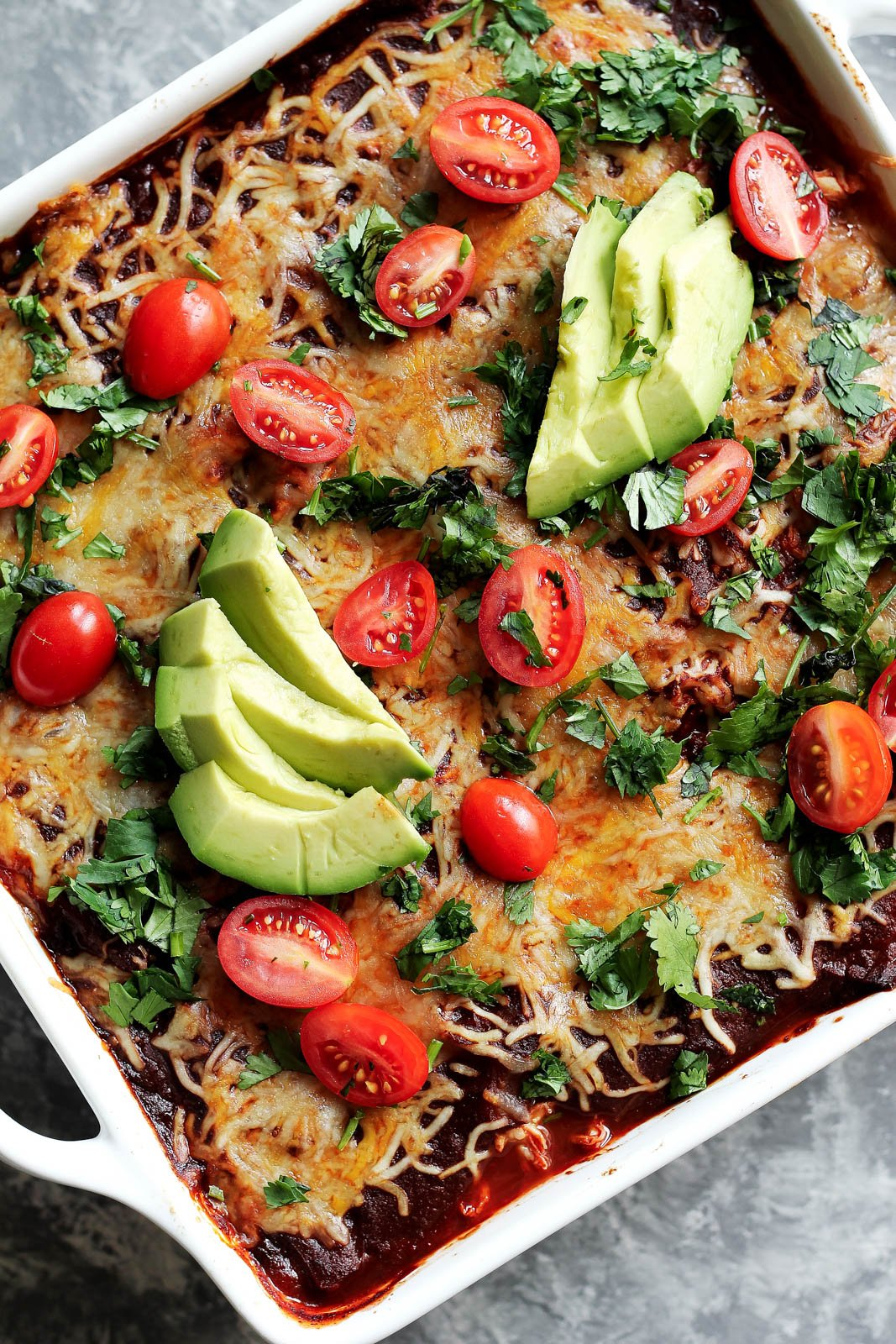 chicken zucchini enchilada bake topped with avocado in a square pan