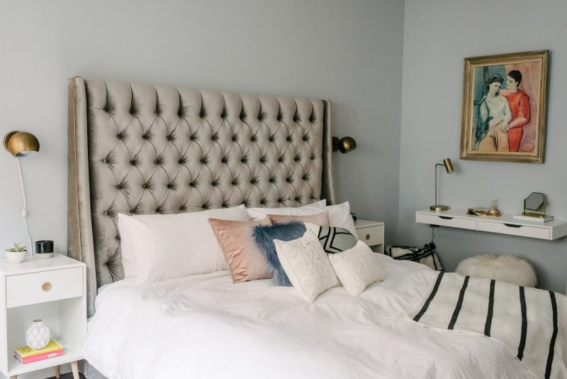 king size bed with throw pillows and a grey headboard