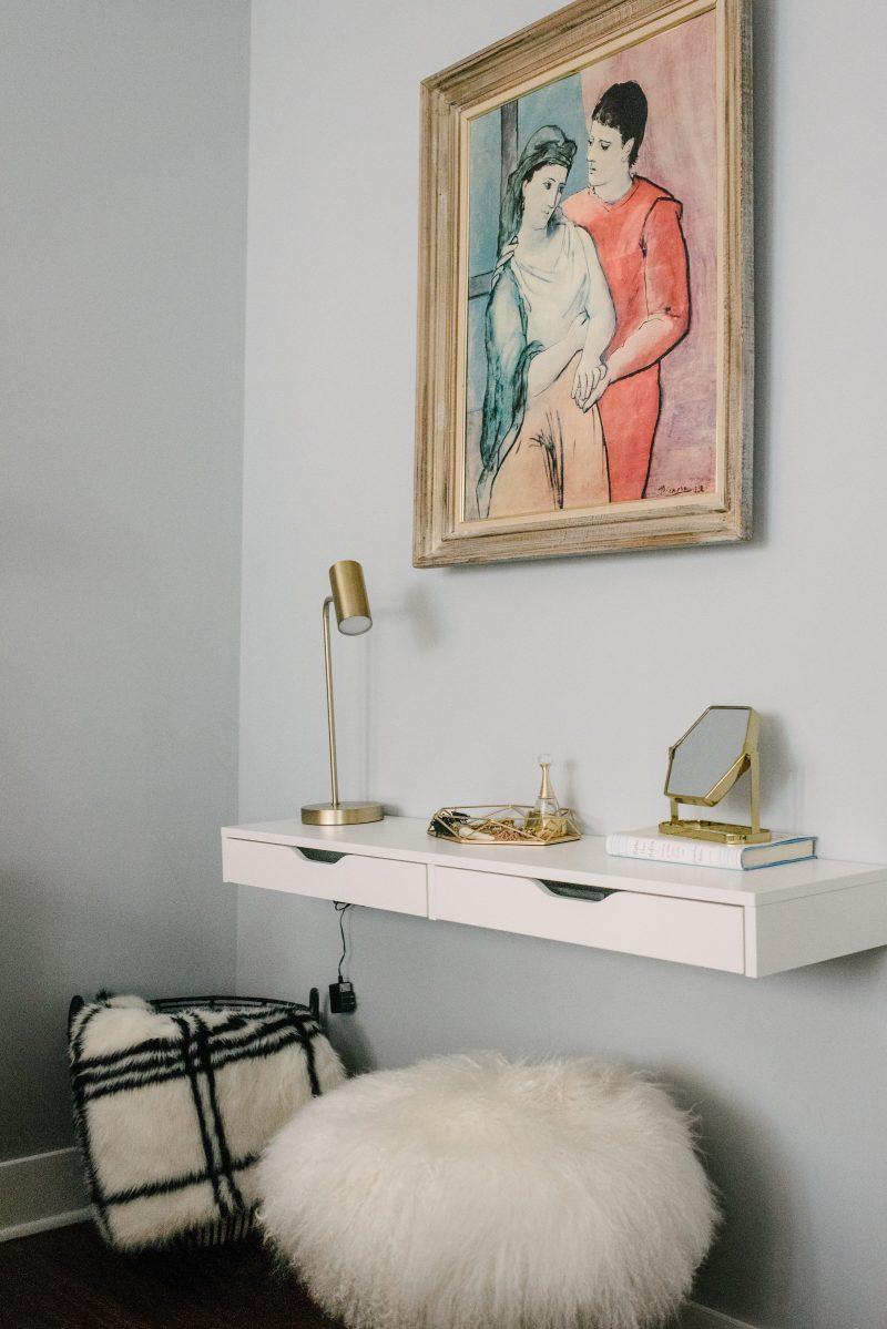 floating shelf with a painting above it and a fluffy white ottoman underneath