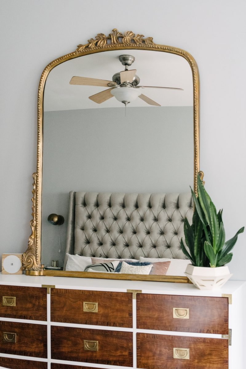 large gold mirror on top of a wooden and white dresser with gold details
