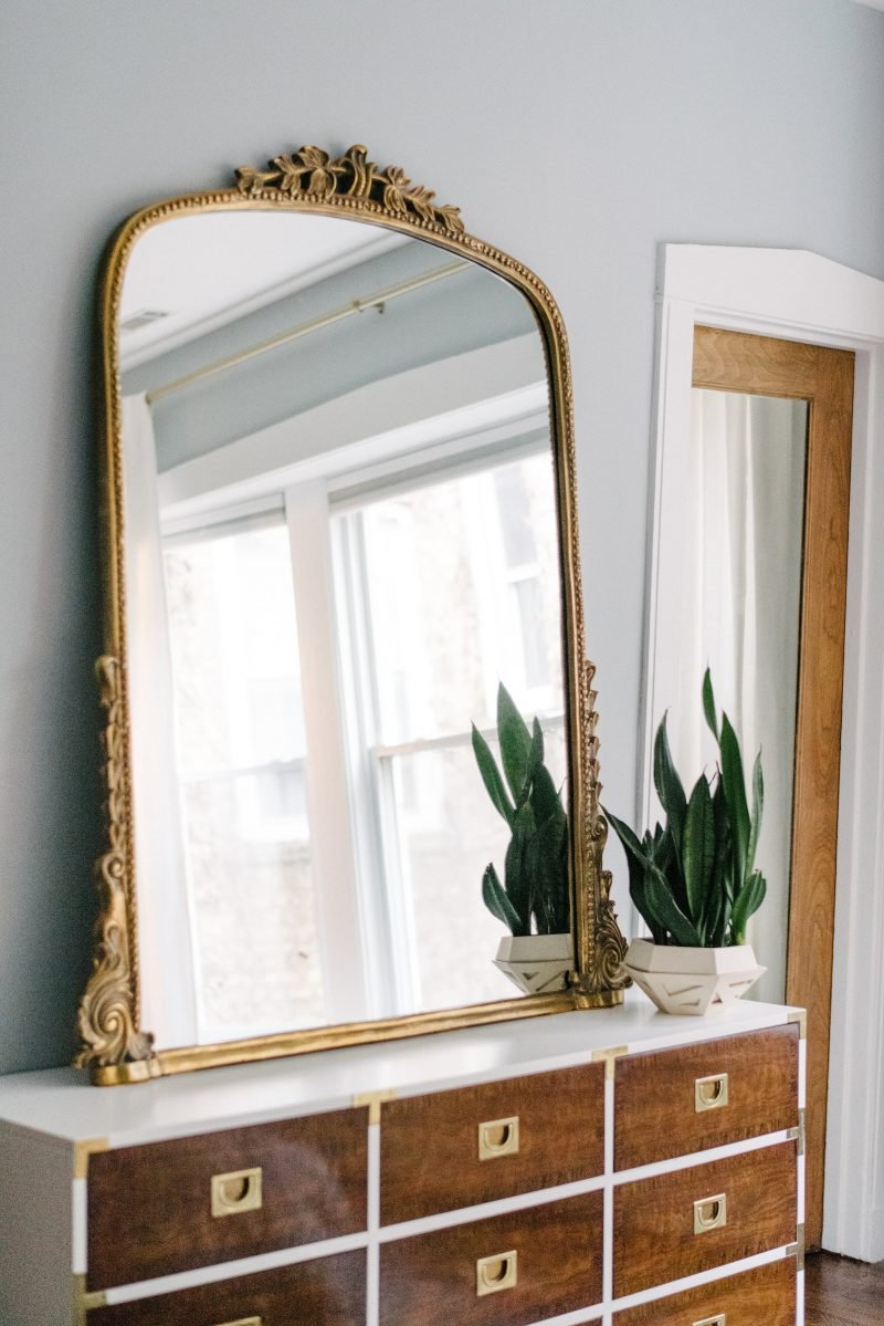 large gold mirror on top of a dresser