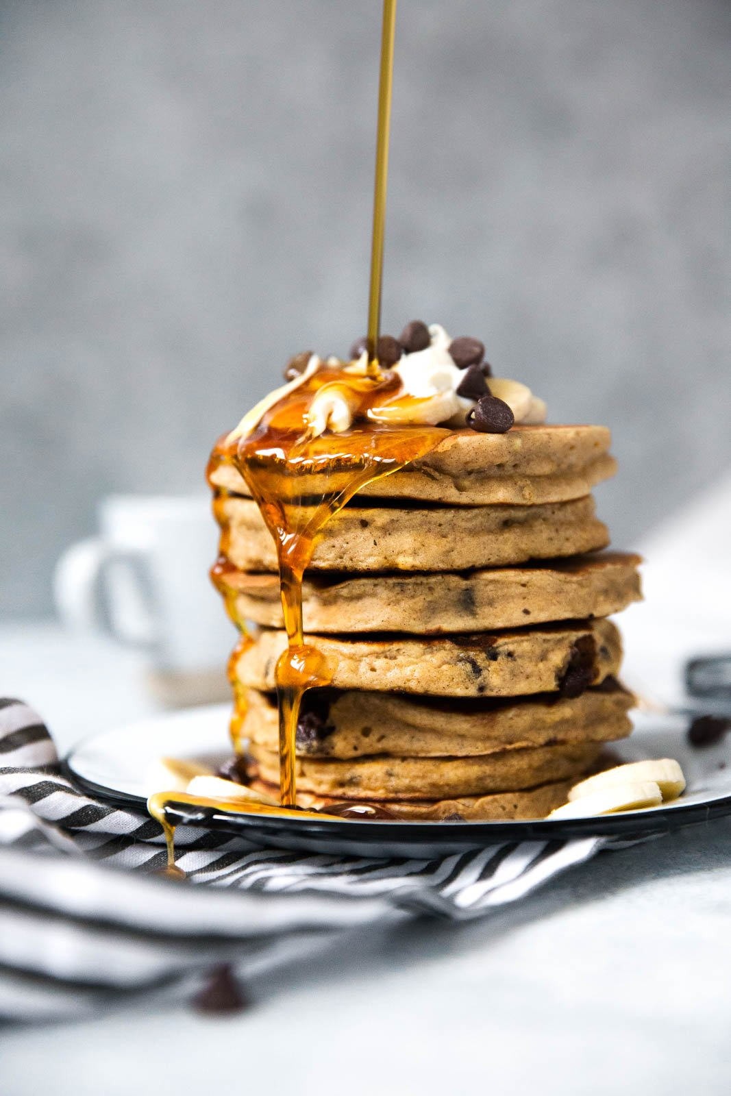 banana bread pancakes in a stack being drizzled with maple syrup