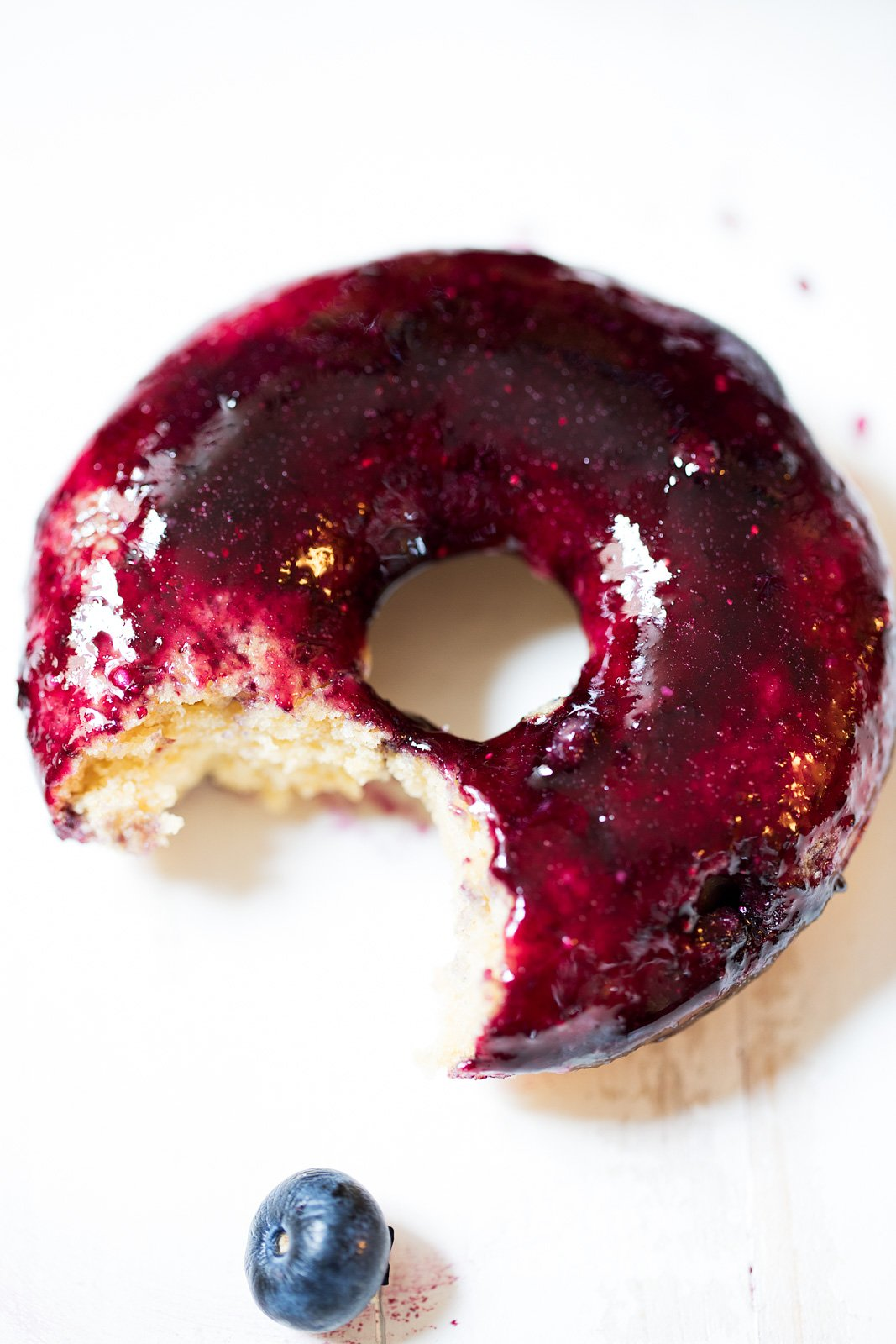 Almond Blueberry Glazed Donuts -- a healthier baked donuts made with a mix of almond and whole grain flour, then dipped in an easy homemade blueberry glaze.