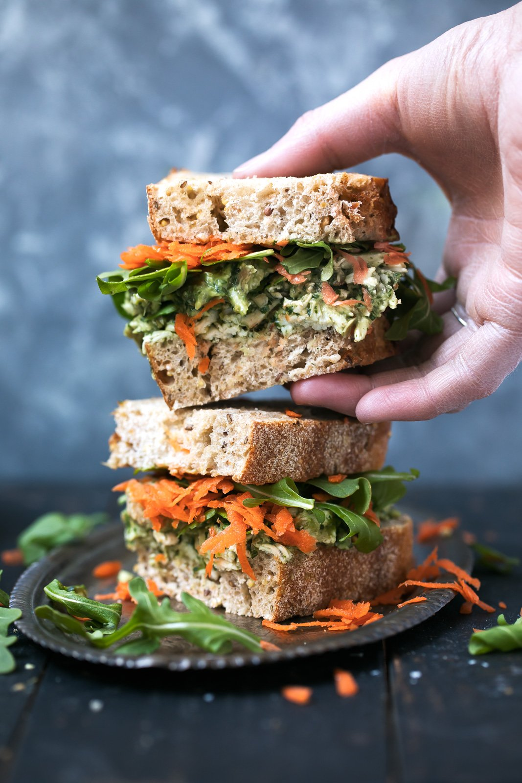 Hand grabbing half of an avocado pesto chicken salad sandwich