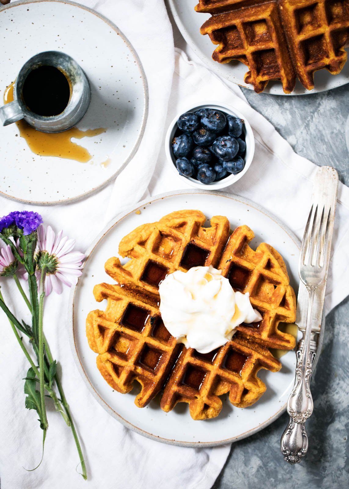 Sweet potato protein waffles topped with whipped cream on a plate