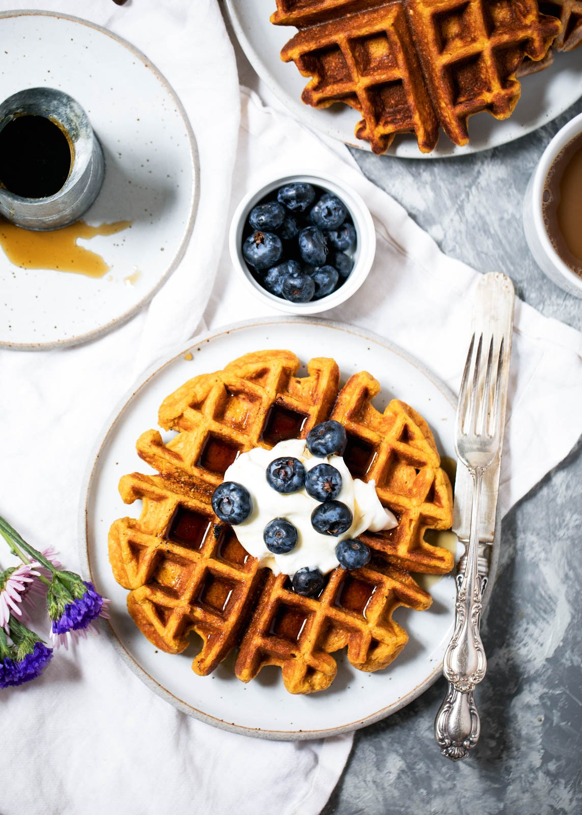 maple sweet potato waffle on a plate topped with blueberries