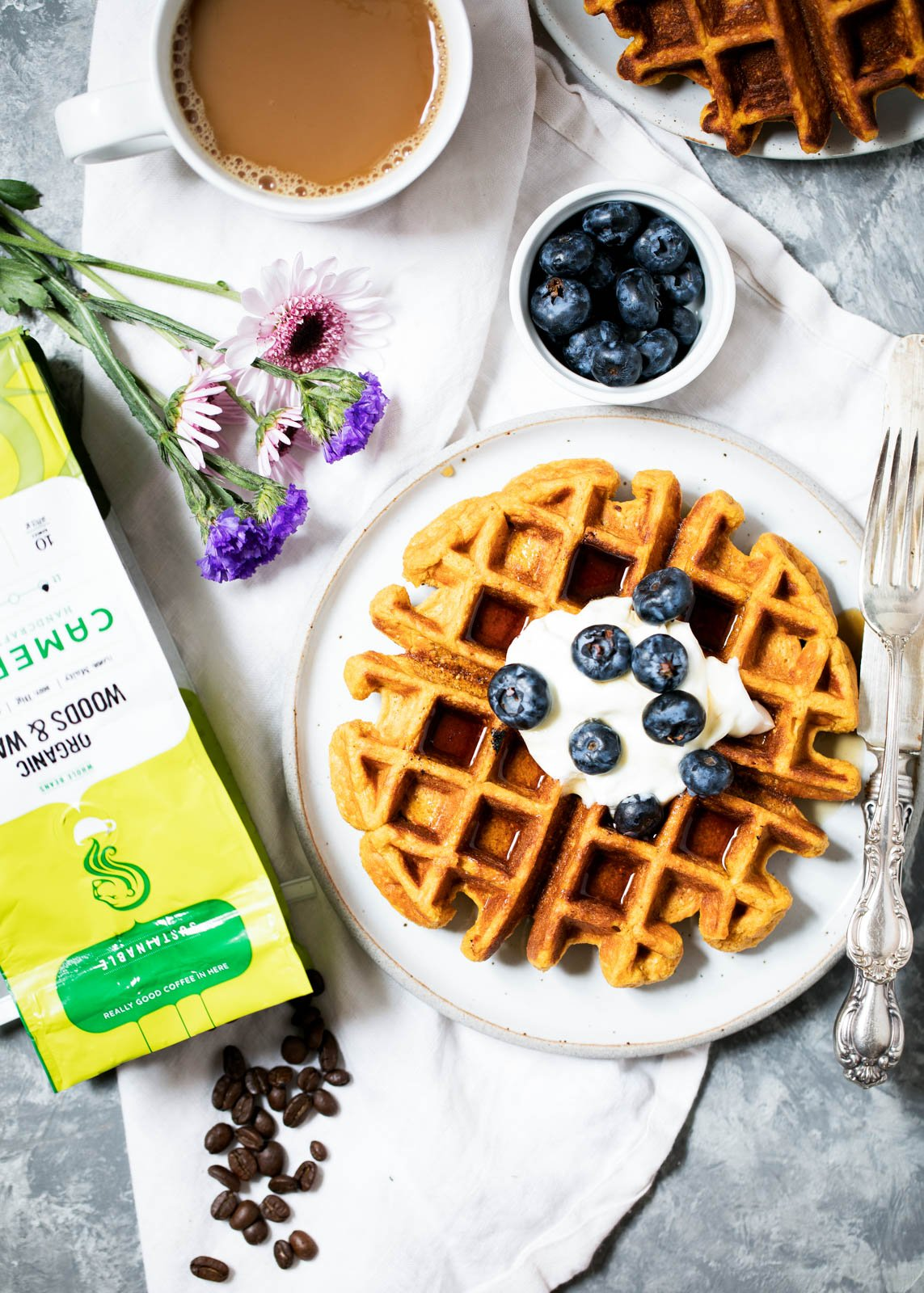 Sweet potato protein waffles on a plate topped with blueberries next to a cup of coffee