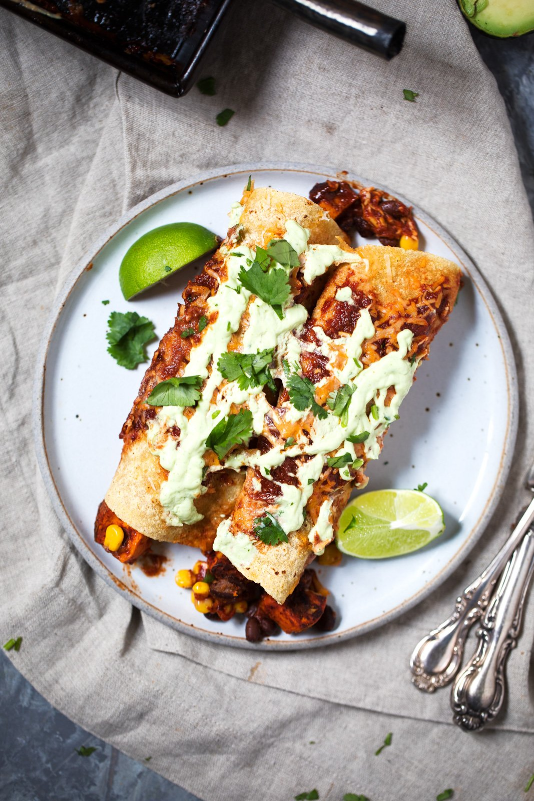 Two enchiladas on a white plate with lime wedges
