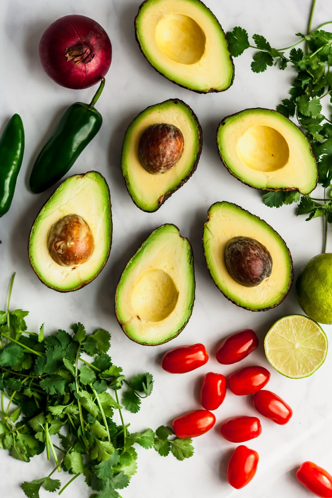 ingredients for the best guacamole on a grey board