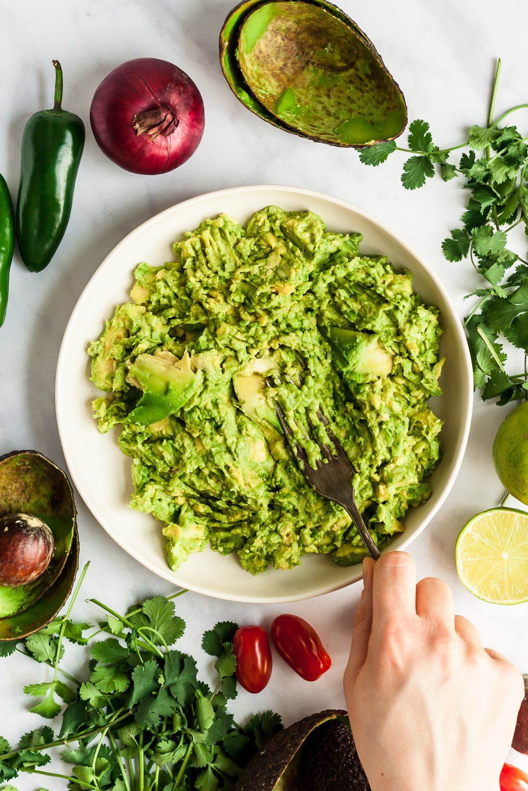 mashing avocado next to ingredients for the best guacamole