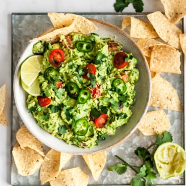 the best guacamole in a white bowl next to tortilla chips