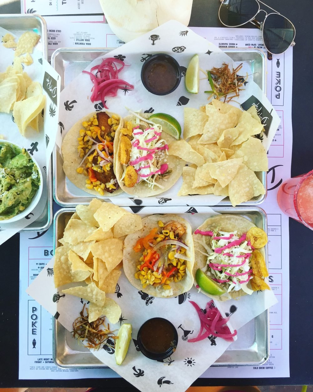two platters of tacos with tortilla chips on a table