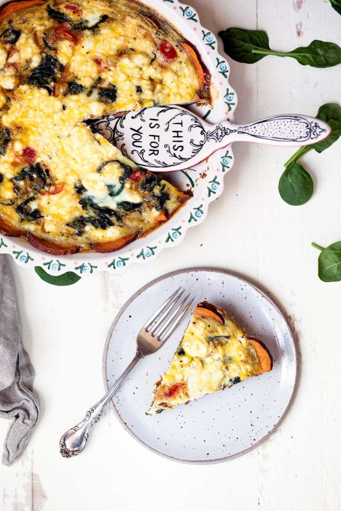low carb spinach and goat cheese quiche with sweet potato crust in a pie pan and on a plate