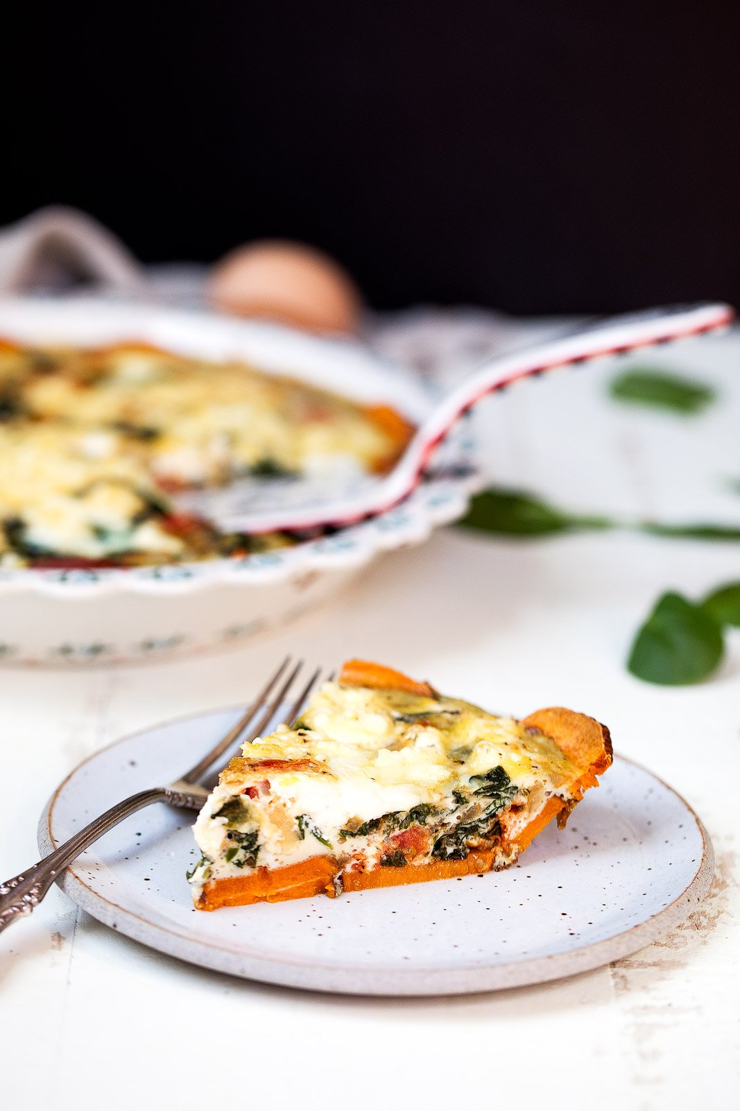 Spinach and goat cheese quiche with sweet potato crust on a plate
