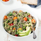 Tuna quinoa salad in a bowl with tomatoes and avocado