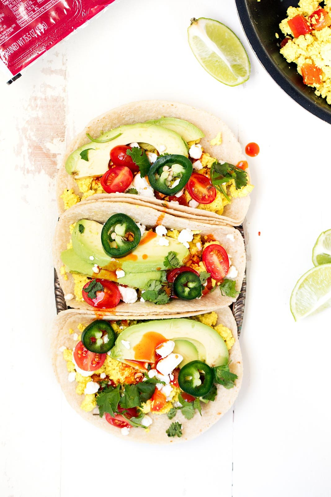 Scrambled tofu with delicious spices gets piled high into corn tortillas and topped with avocado, cilantro and so much more! Easy to make ahead and reheat for an on the go breakfast.