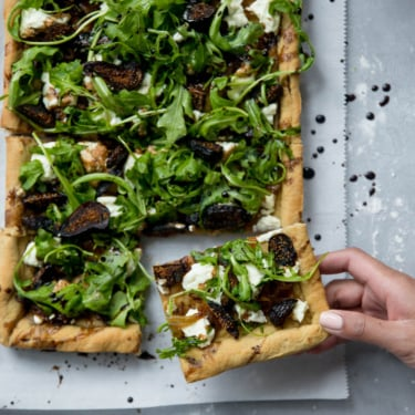 goat cheese pizza topped with arugula, goat cheese and figs