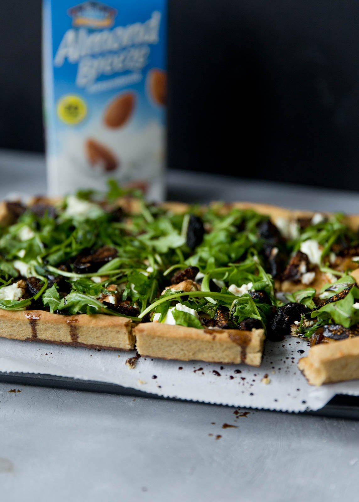 goat cheese pizza topped with arugula and figs with an almond breeze carton in the background