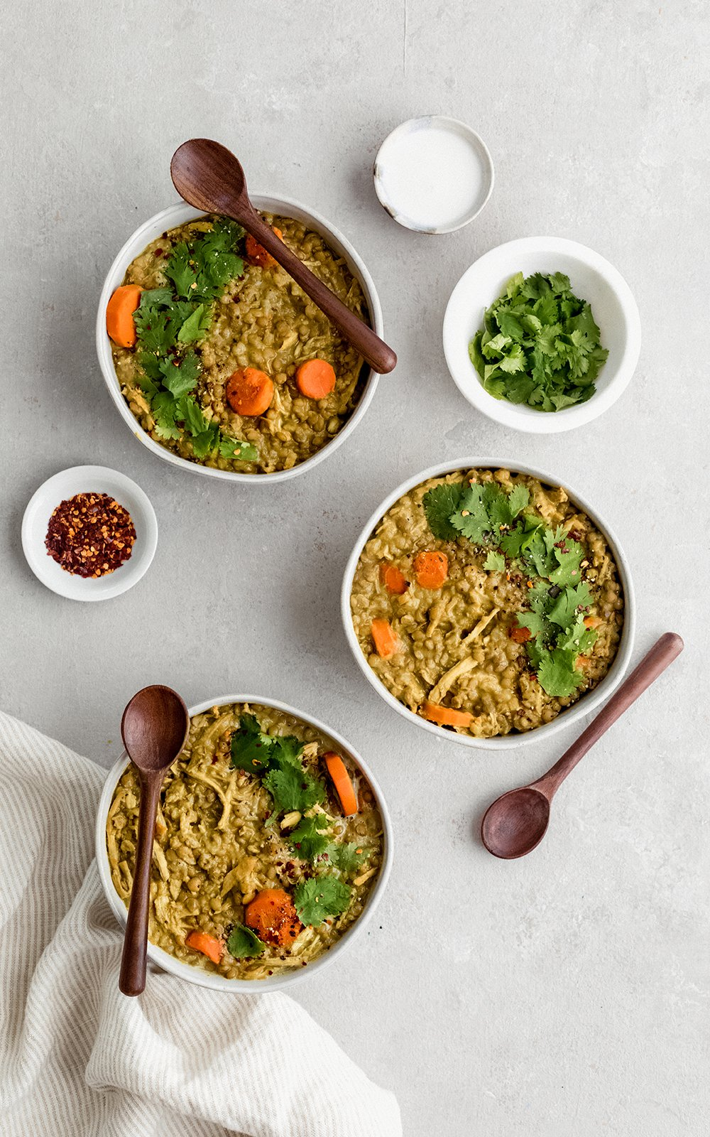 three bowls of chicken lentil soup with wooden spoons