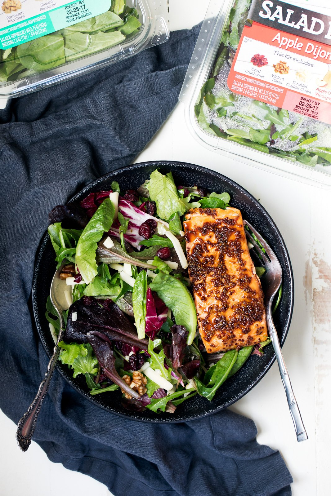 honey garlic salmon over a salad in a bowl next to a salad kit