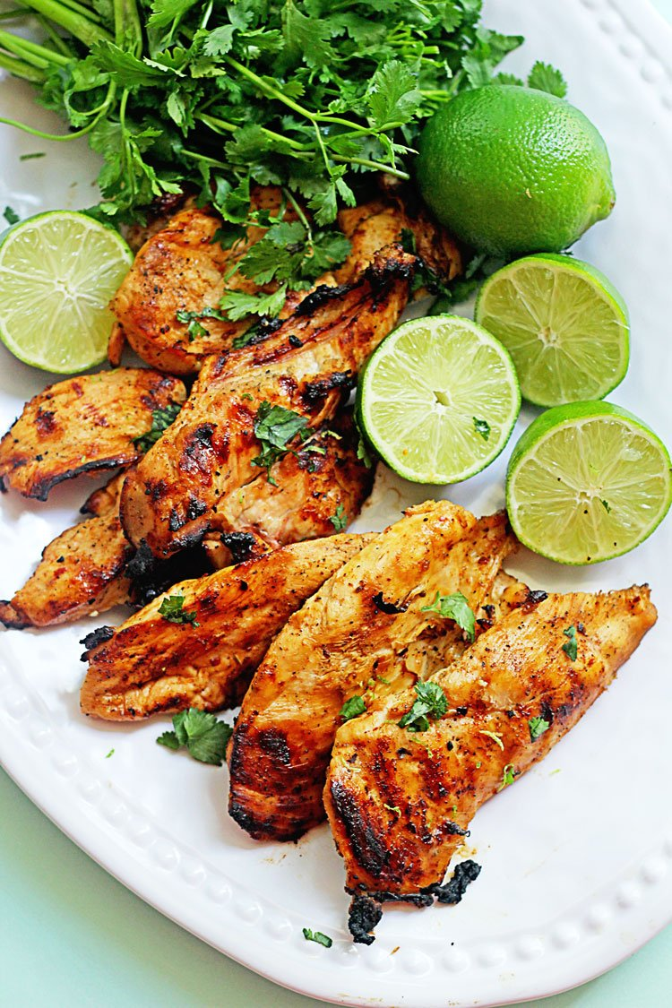 chicken on a plate with limes