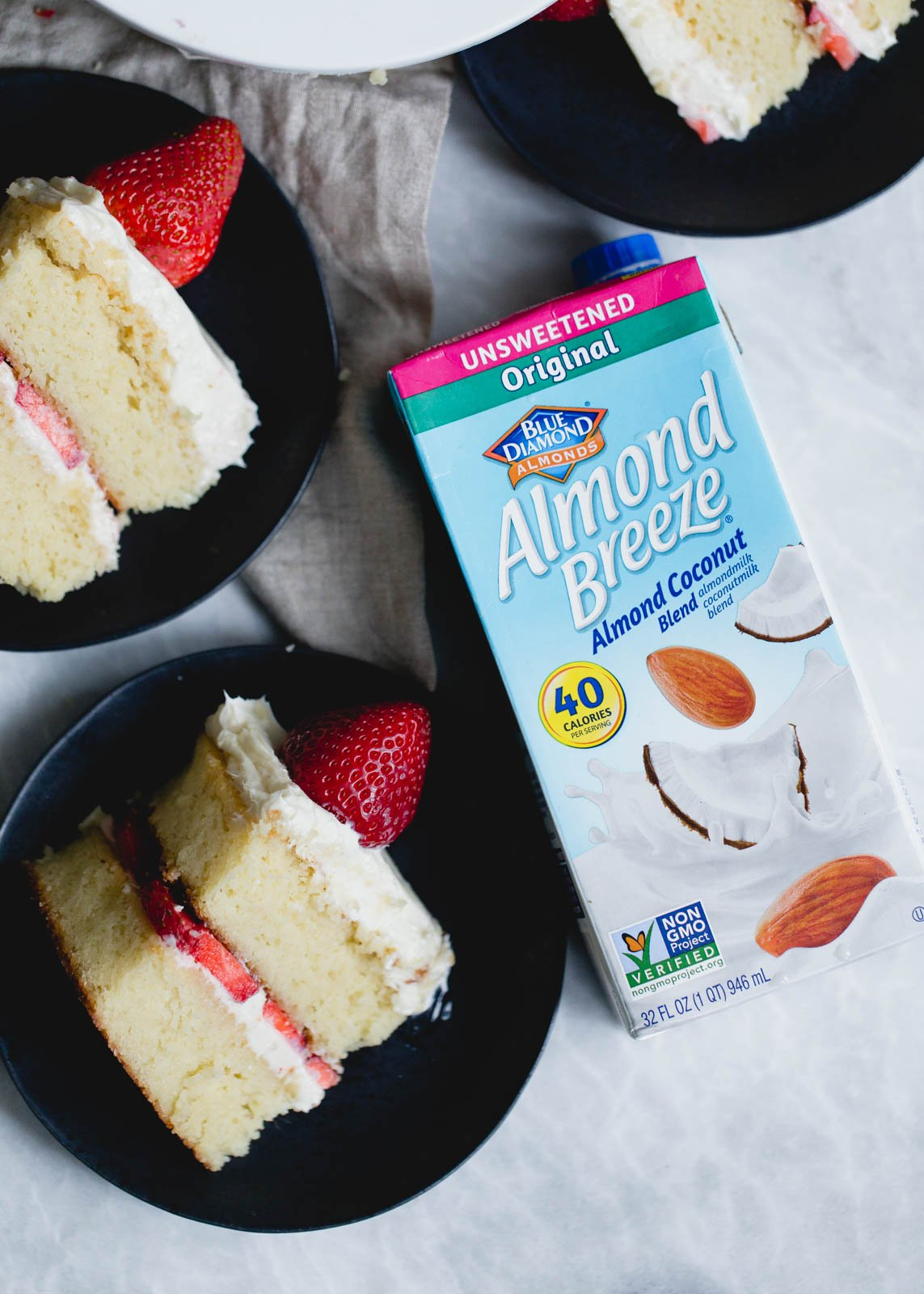 paleo-friendly strawberry shortcake cake slices on two plates next to a carton of almond breeze almond coconut milk