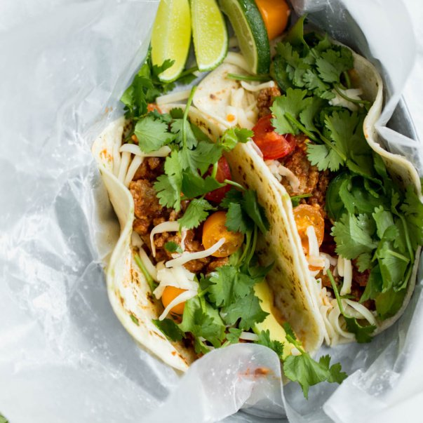 slow cooker turkey tacos in a container with parchment paper