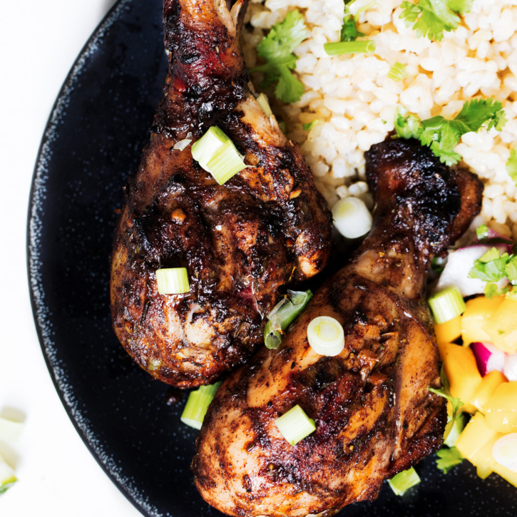 marinated chicken drumsticks on a plate with rice