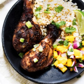 grilled jerk chicken drumsticks with rice and mango salsa in a bowl