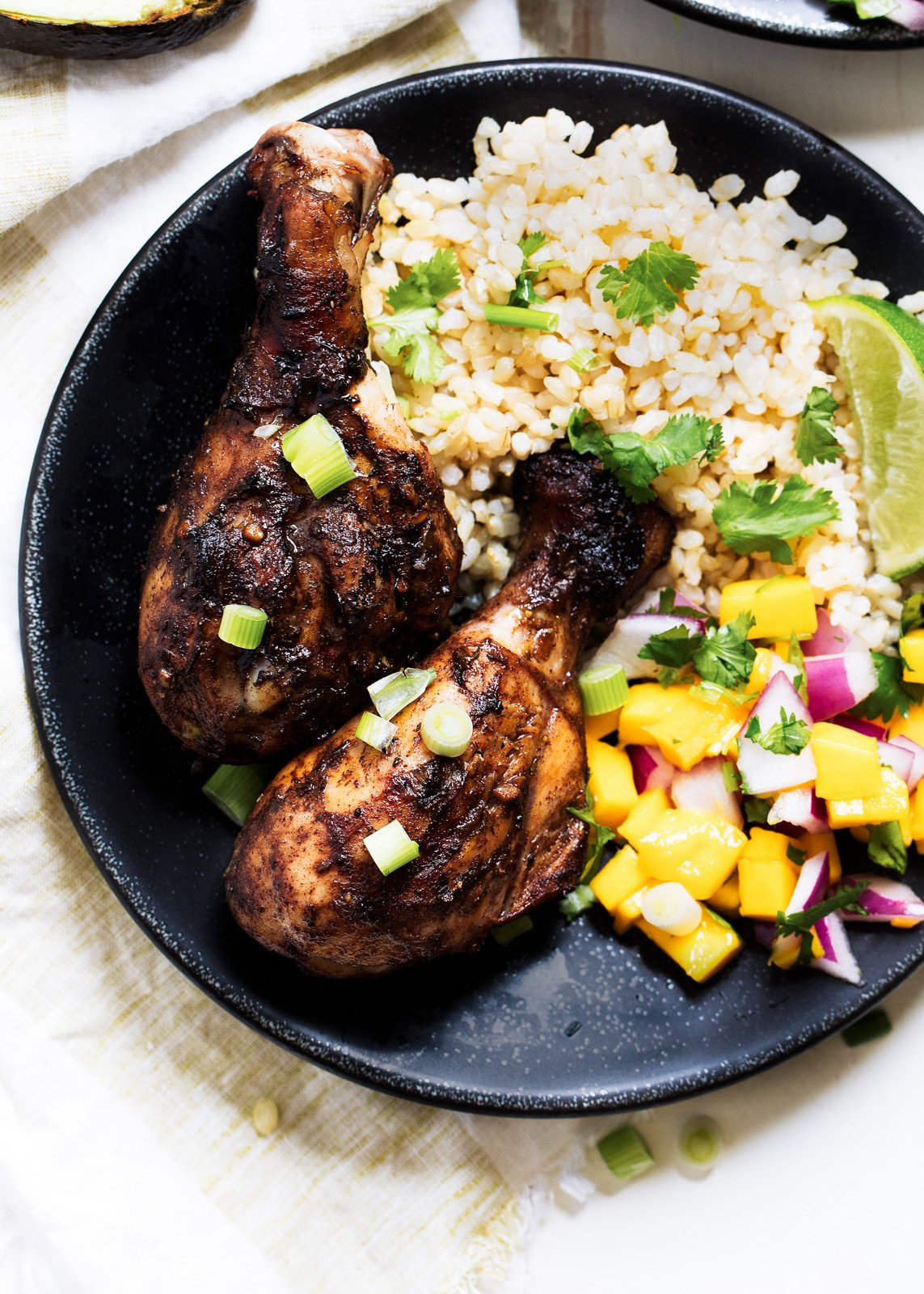 Juicy grilled jerk chicken drumsticks with a delicious Caribbean Rice & sweet mango salsa. The perfect healthy grilling recipe for summertime!