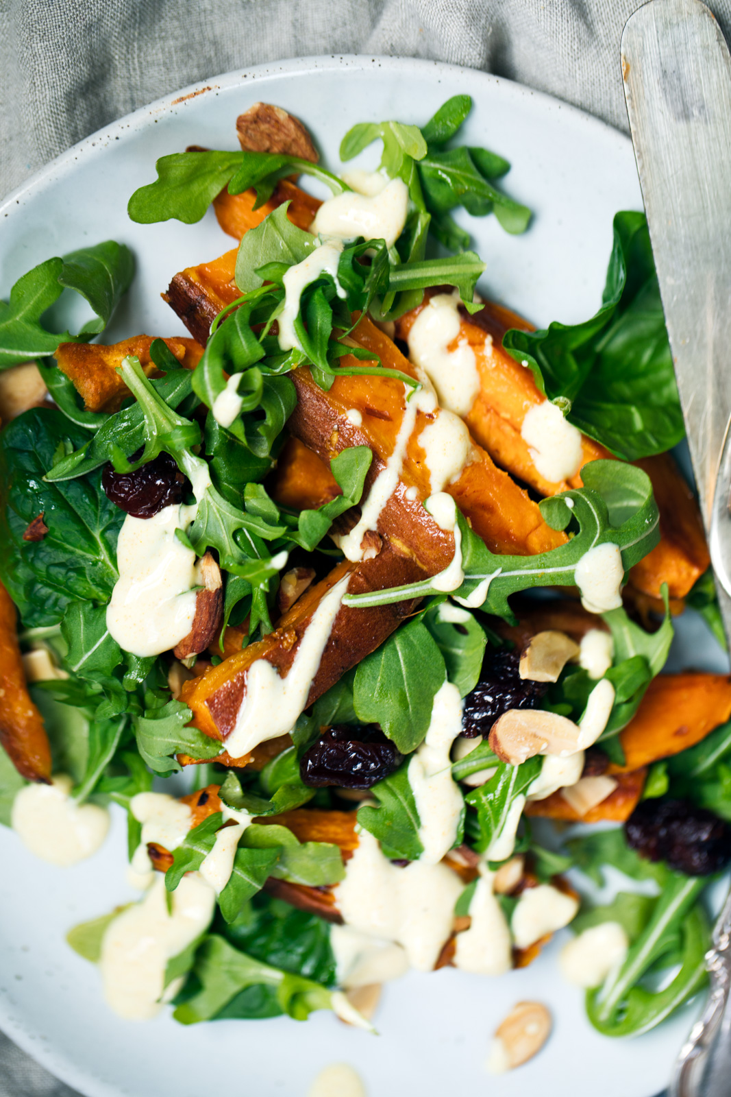 Roasted sweet potato arugula salad is a perfect lunch or appetizer. Topped with a light honey mustard yogurt dressing with a hint of gorgeous turmeric color.