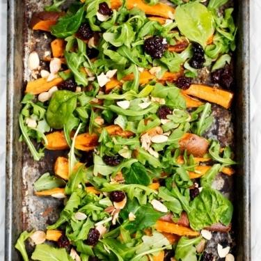 Roasted sweet potato arugula salad on a baking sheet