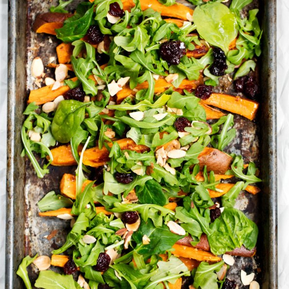 Roasted sweet potato arugula salad on a baking sheet