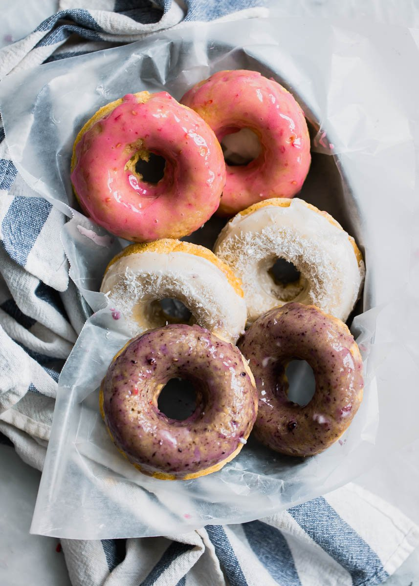 Baked coconut donuts with a sweet berry glaze on parchment paper
