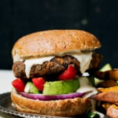 Delicious veggie packed vegan black bean burgers with plenty of spices. I call these the ultimate black bean burger. Top with avocado, onion, tomato and a super addicting garlic tahini sauce!