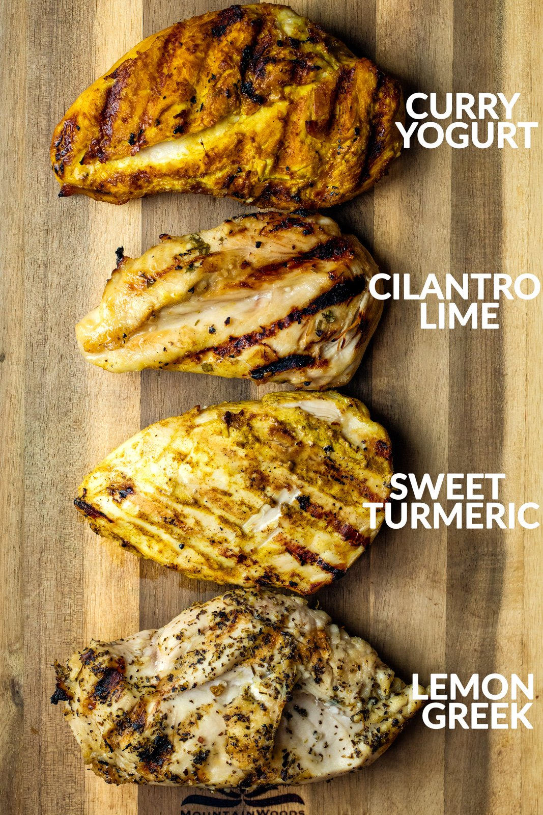 Four pieces of grilled chicken on a wooden platter