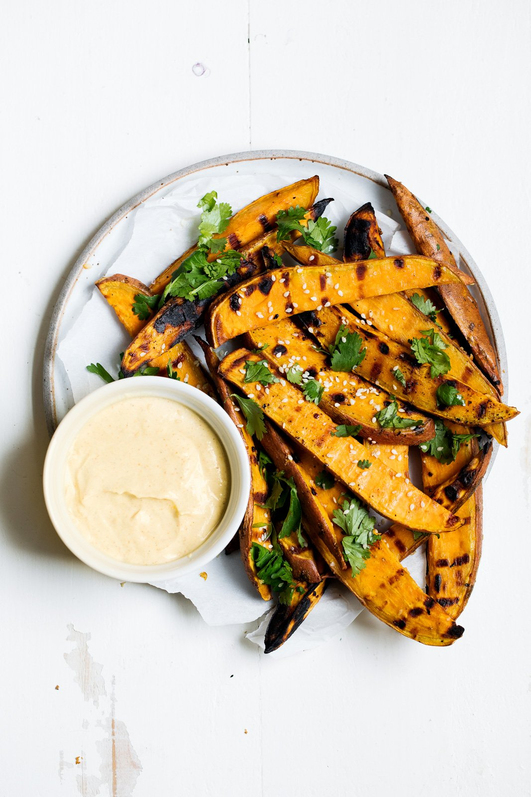 grilled sweet potato fries on a plate with yogurt curry dip