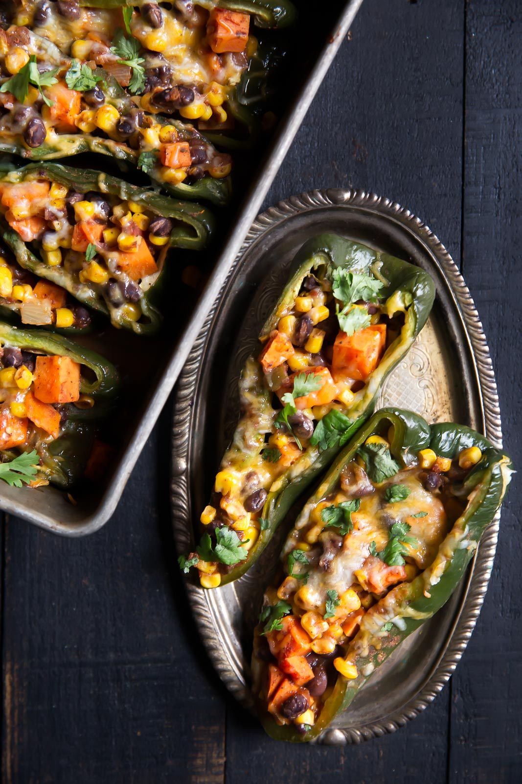 Two poblano peppers stuffed with vegetables and cheese on a small silver platter