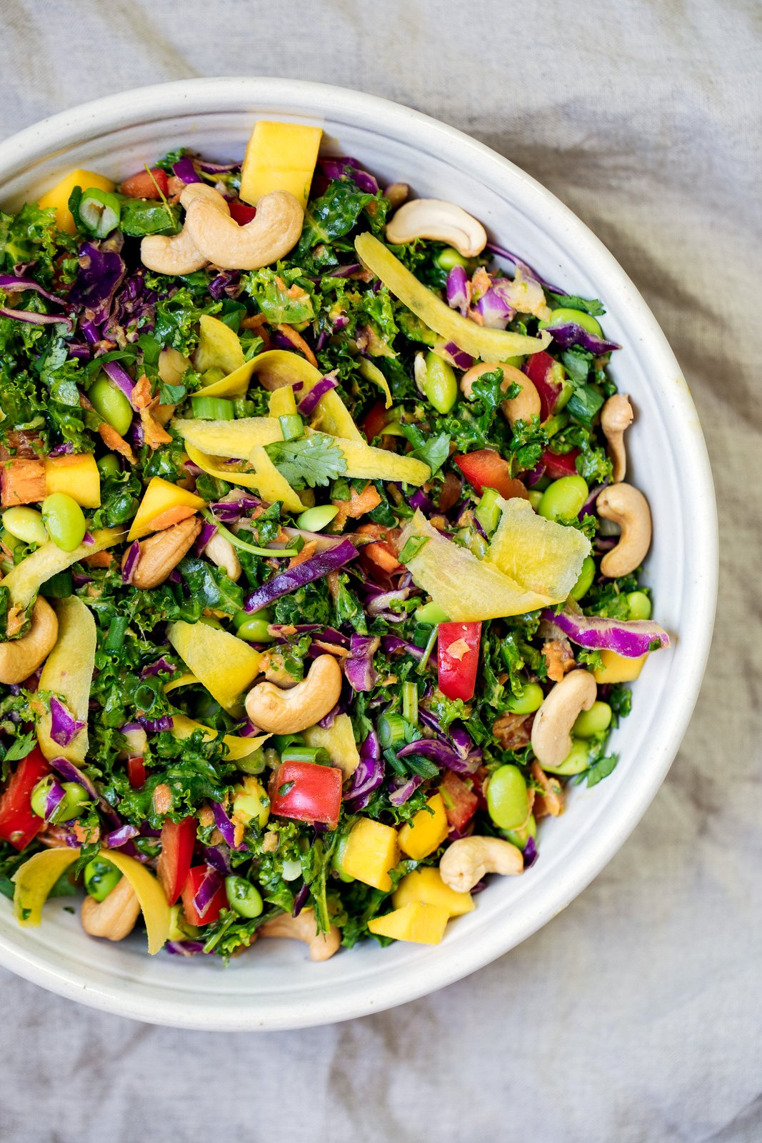 Chopped kale salad with cashews in a white bowl