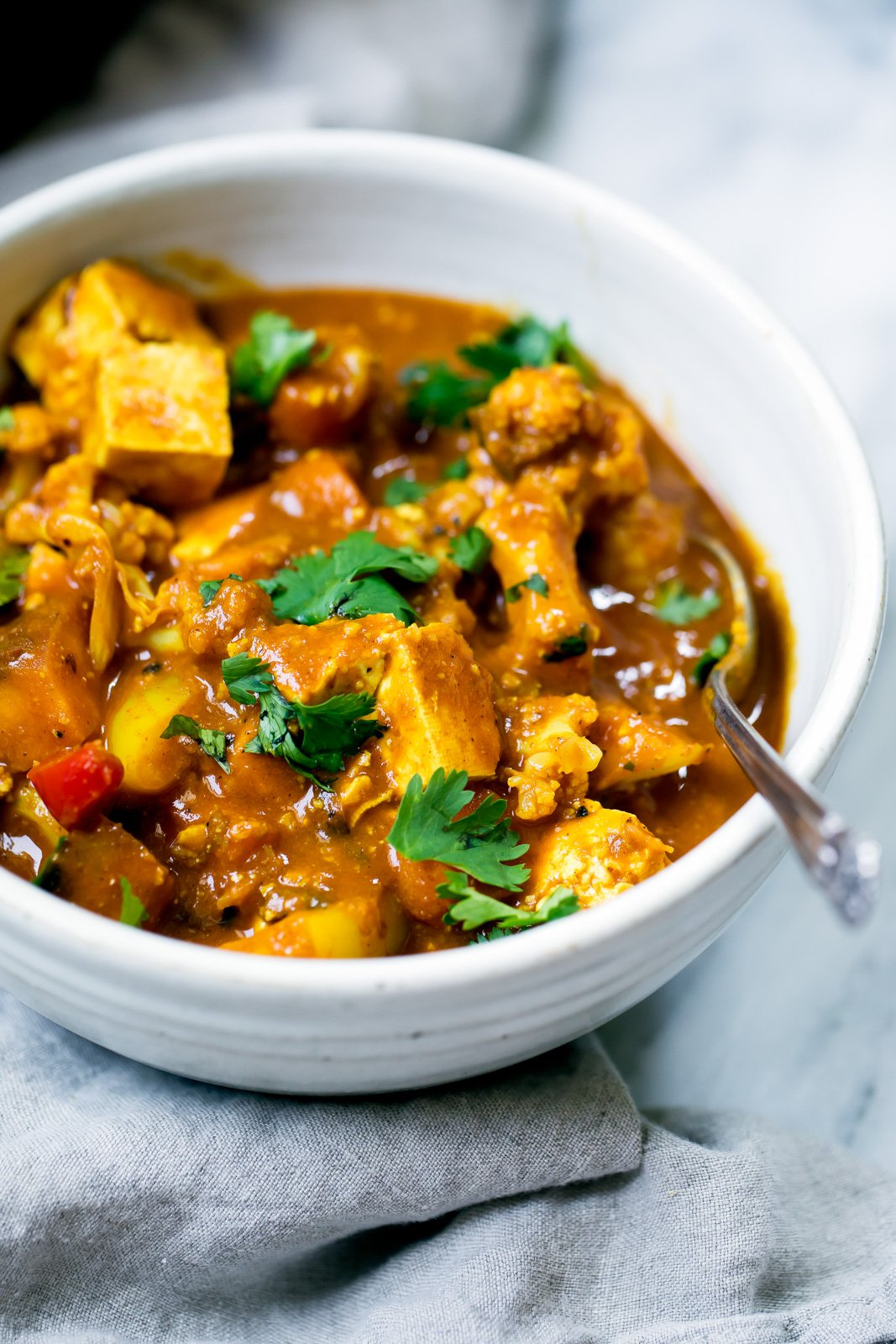 tofu and cauliflower curry in a white bowl with a silver spoon