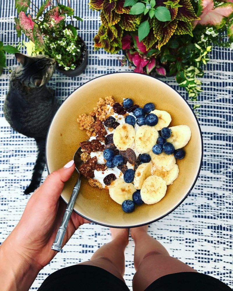 bowl of yogurt with banana slices, blueberries and granola